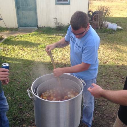 Stirring the pot of crawfish, sipping some beers